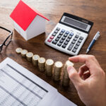 Person Stacking Coins Near House On Wooden Desk Computing Taxes