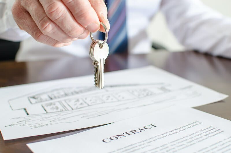 cash buyer holding house keys over a contract