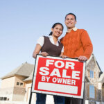 couple with for sale by owner sign selling house on their own