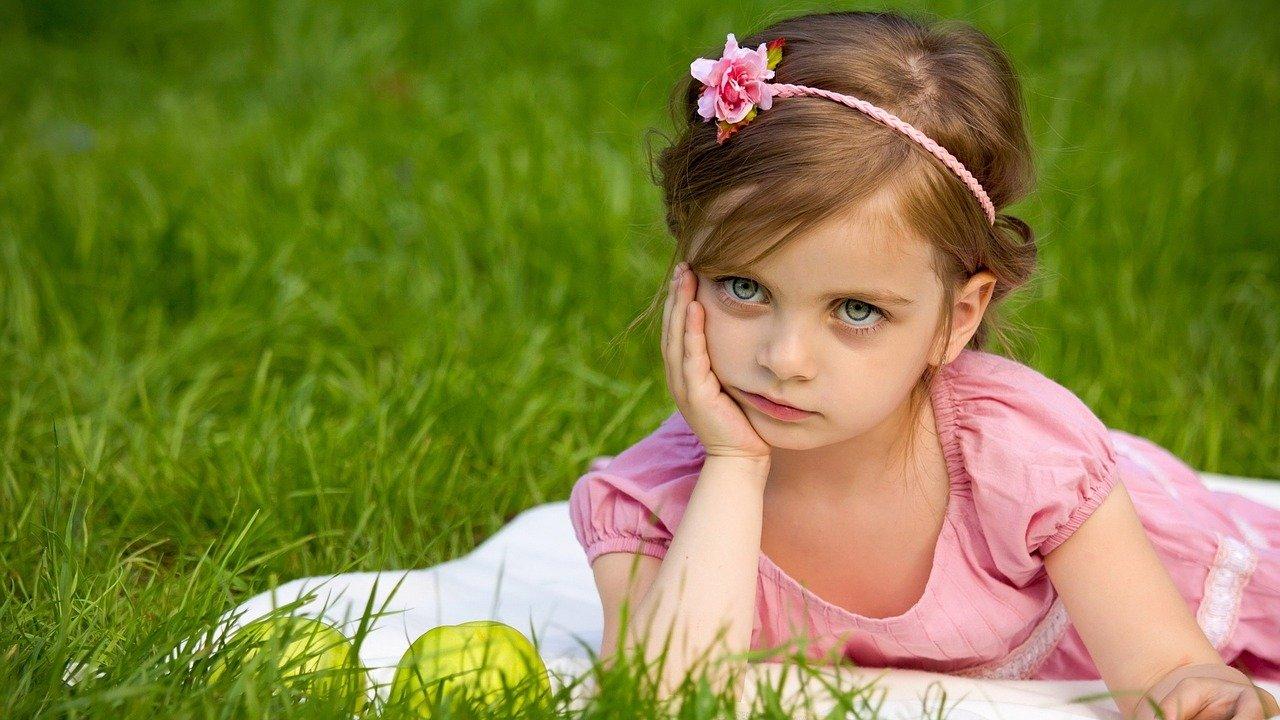 cute little girl posing in pink dress outdoor sitting in green grass