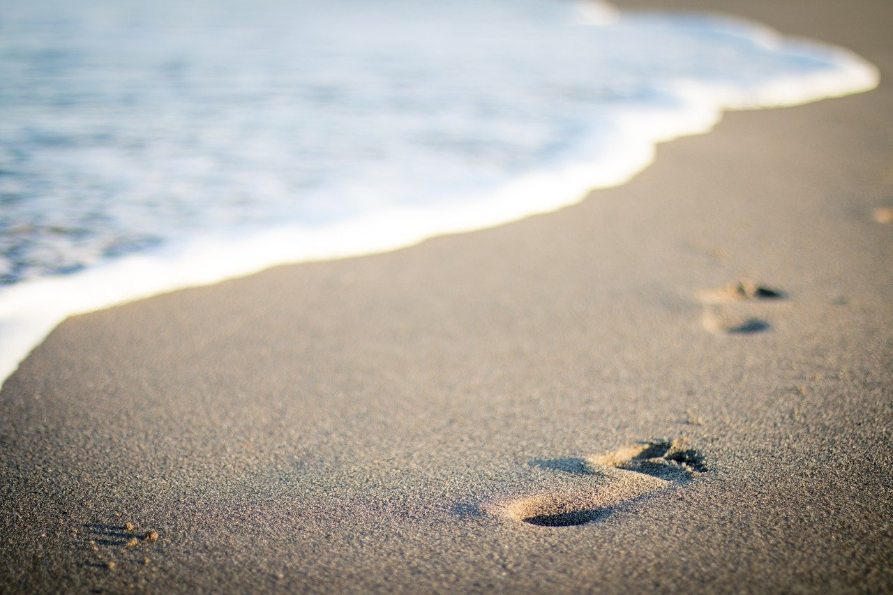 close up of human foot print on beach sand