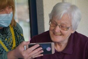 An older woman looking at a phone smiling