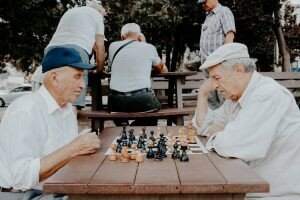Two older men who have gone through downsizing in Kansas City and are now playing chess outside of a retirement home