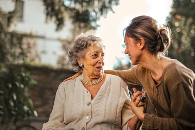 An older woman engaging in a heartfelt conversation with her daughter