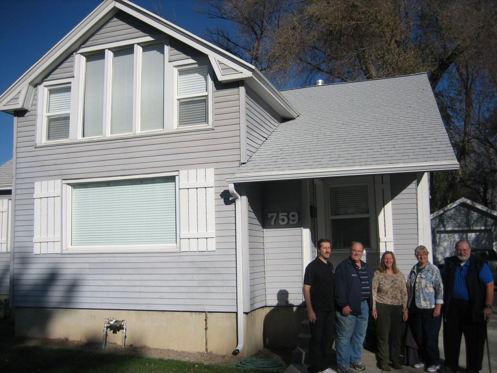 Five brothers and sisters standing in front of a house they sold quickly in Utah to Gary Buys Houses.