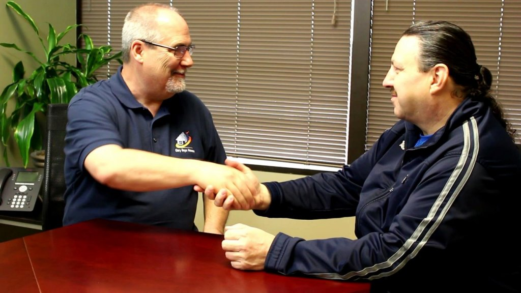 Company owner Gary Parker shaking hands with a client who sold their house to Gary Buys Houses