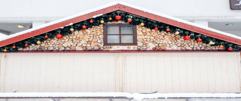 front of house in snow with holiday decorations