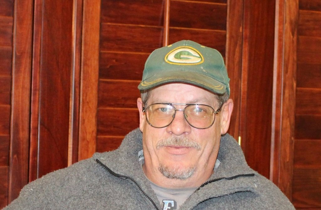 man name Thomas in a green baseball hat sitting in an office to stop foreclosure