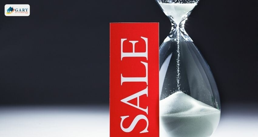 """hourglass next to a sign reading """"sale"""""""