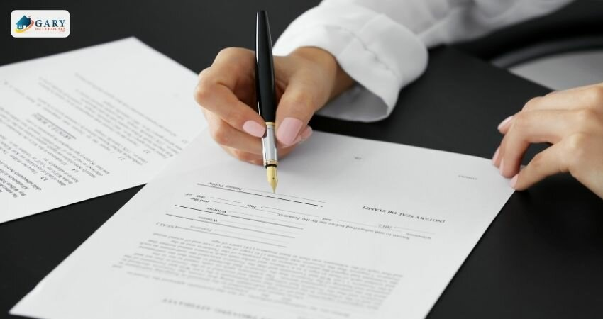 woman signing a document at a table