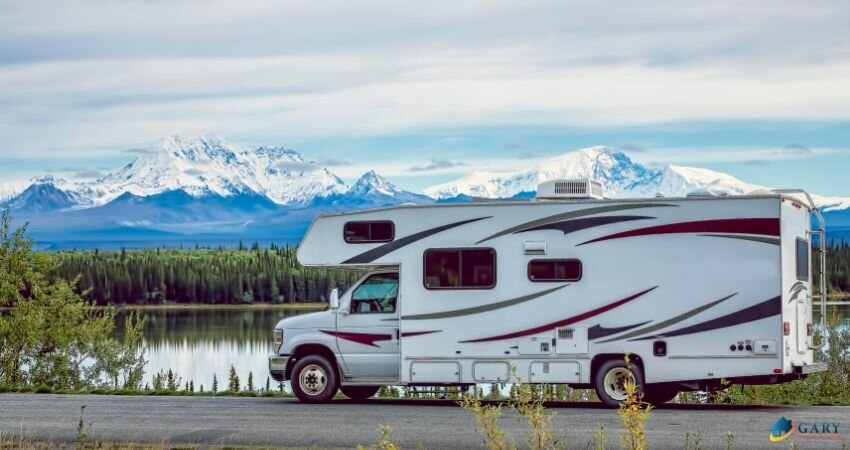 Rv parked on road with mountains behind lake and trees.