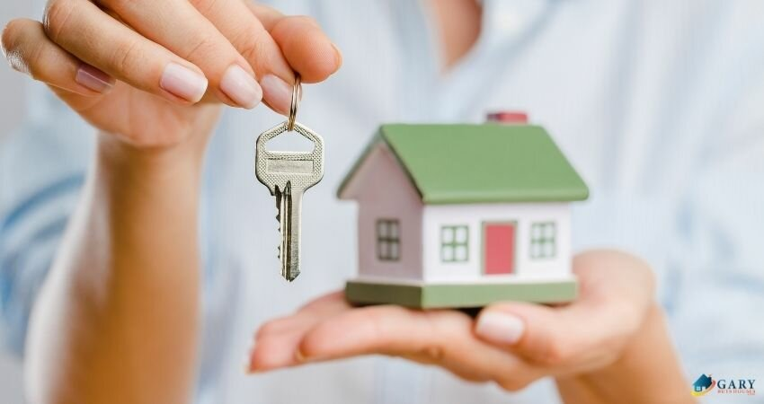 hand holding a key and the other hand holding a mini house as a symbol of selling your house.