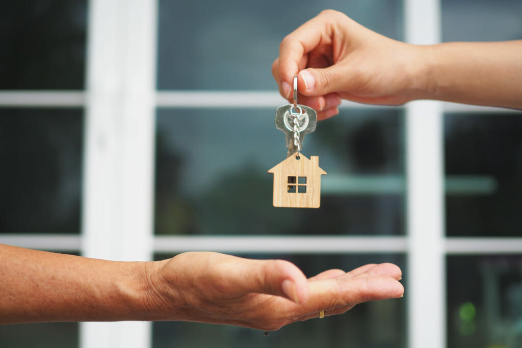 A person handing over the keys to their house to another person with an opened hand