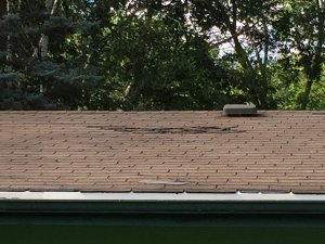 Missing and damaged shingles on roof of fixer upper