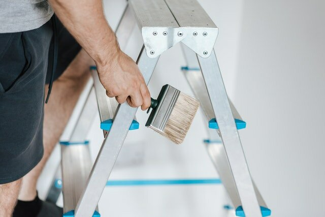 Man climbing on a ladder and holding a paintbrush