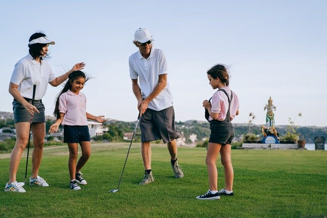 A family playing golf in one of the best places to raise a family in Greensboro, NC