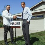 Two people shaking hands in front of a house, next to a sign showing the house has been sold