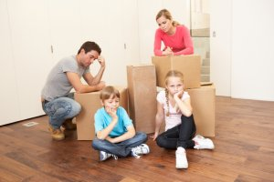 Young family looking upset among boxes