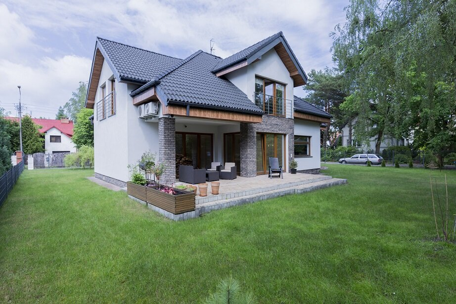 Detached modern house exterior with terrace surrounded trimmed green lawn