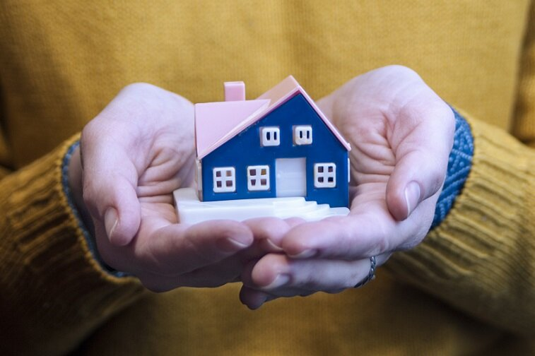 A person holding a miniature home in her hands