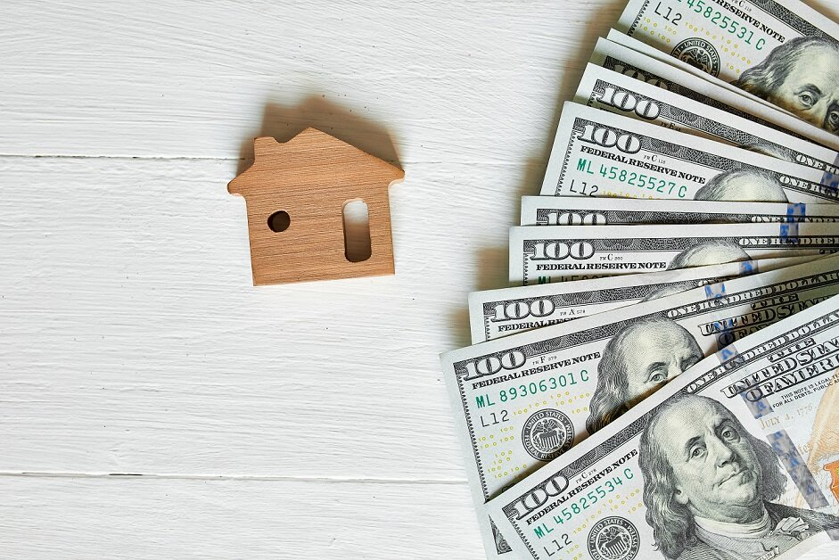 Small wooden house and hundred dollar on white background, concept of real estate, growth of mortgage credit, Property investment and house mortgage financial concept.