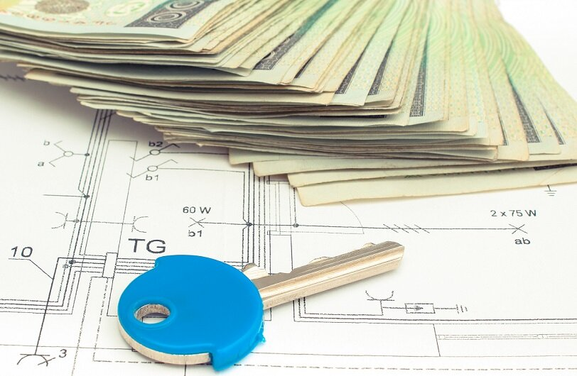Electrical construction drawings of house, polish currency money and home key, concept of building home cost