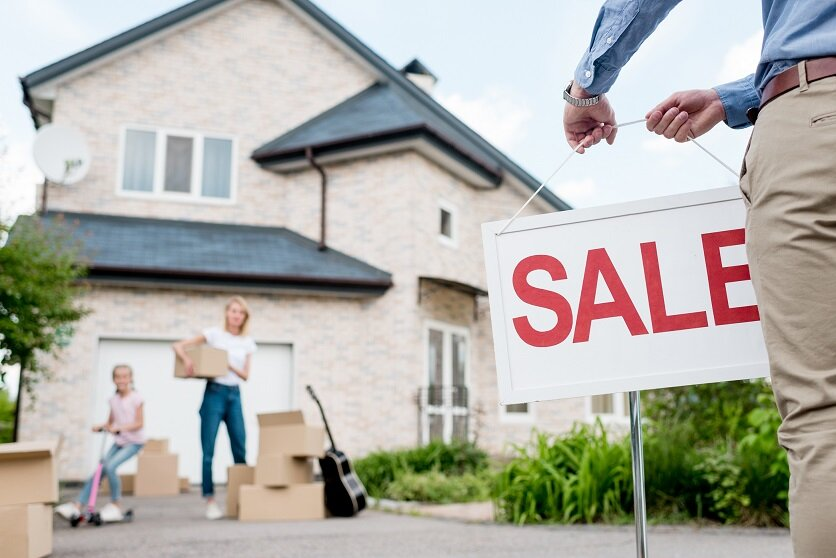 cropped image of male realtor with sale signboard and family with cardboard boxes behind