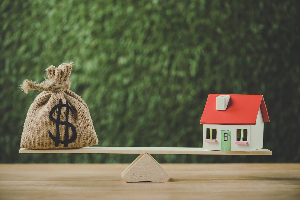 money bag with dollar symbol and house model balancing on swing on green background