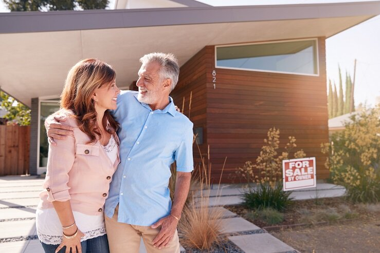 Senior Couple Standing Outdoors In Front Of House With For Sale Sign In Garden