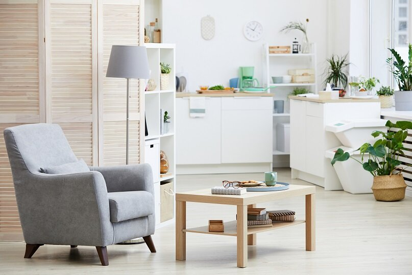 Image of armchair and wooden table in the living room with modern kitchen in the background