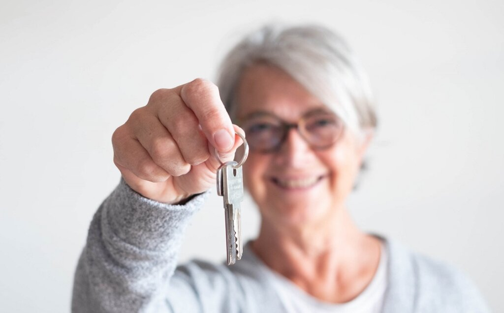 close up of mature woman holding a couple of keys of her new house or home or some property - indipendent senior