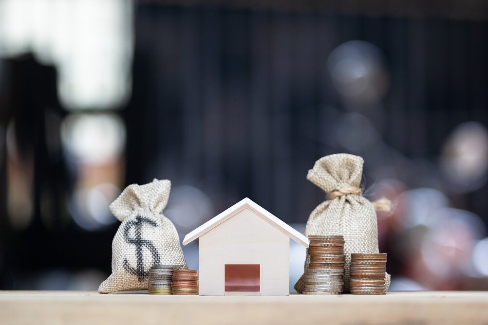 Home loan, mortgages, debt, savings money for home buying concept. Dollar money bag, small residential, house model and coins on table against green nature background. Exchange of finances and houses.