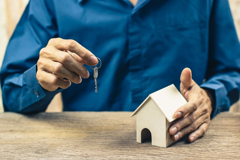 New home buying concept. Estate agent giving house and key. Depicts the completion of the agreement in the home trading.