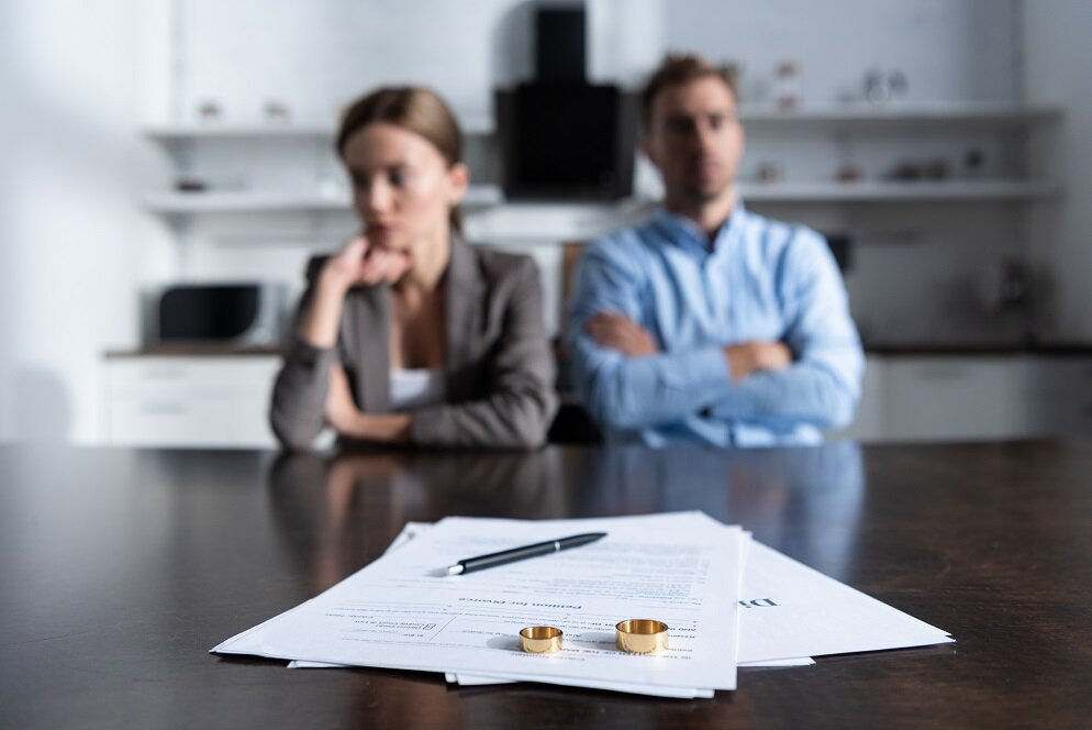 selective focus of couple sitting at table with divorce documents