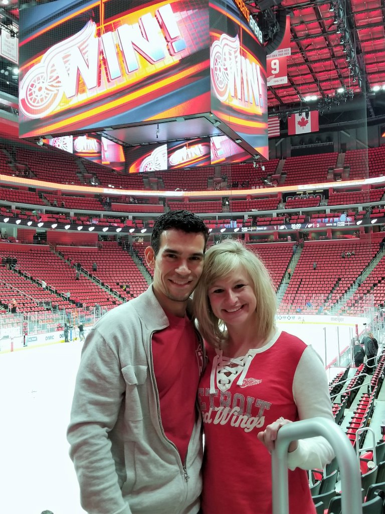 Founder of Amaze Properties LLC and josephbuyshomes.com, Joe Mazur and wife standing in hockey arena in Detroit MI