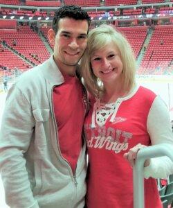 Founder of Amaze Properties LLC and josephbuyshomes.com, Joe Mazur and wife standing in hockey arena in Detroit MI