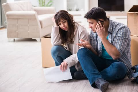 sad couple looking at house foreclosure letter in detroit