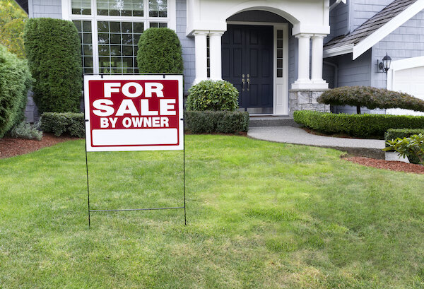 a house with a for sale by owner sign