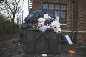 An overfilled dumpster in New Brunswick, NJ. With Templar Real Estate Enterprises, you can sell your house without having to worry about stinky smells!