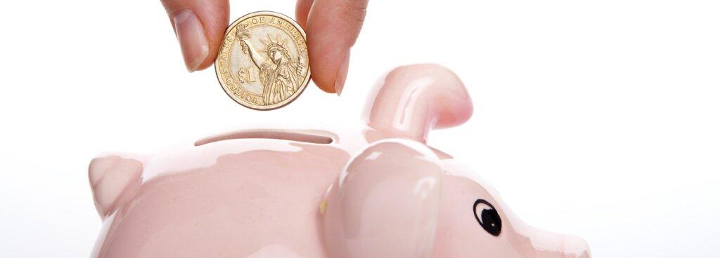 $1 coin going into piggy bank