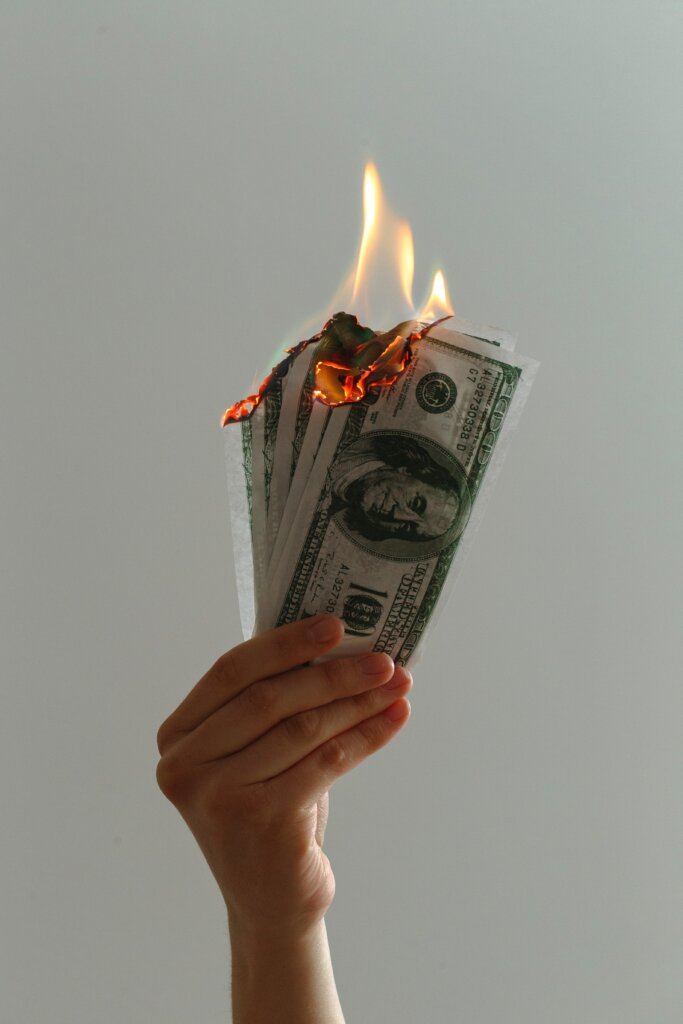 Person burning money in hands to symbolize debt from foreclosures.