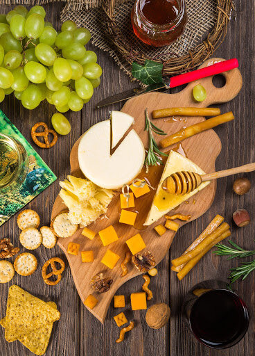 Cheese plate spread with crackers, honey, and grapes for an open house.  When you sell your house to Templar Real Estate Enterprises, there is no need to hold an open house!