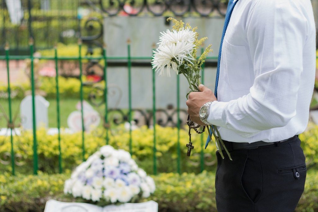 man with flowers at cemetery
