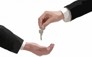 A real estate agent handing keys to a client