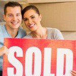 How To Sell A House Off Market | smiling couple holding sold sign