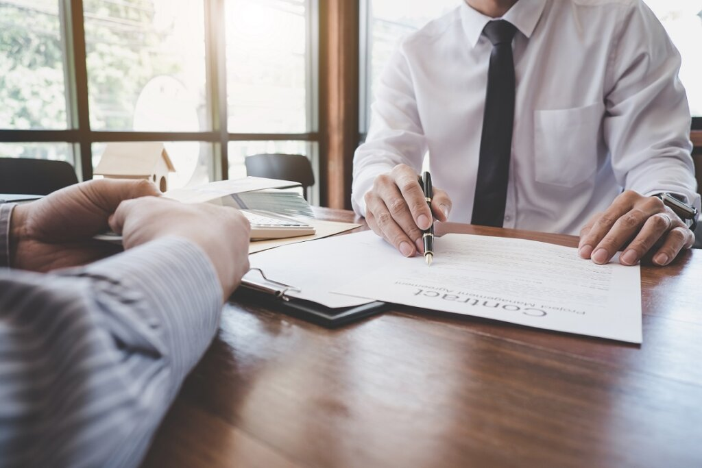 Business Signing a Contract Buy - sell house, Man sign a home insurance policy on home loans, insurance agent analyzing about home investment loan Real Estate concept.