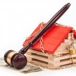 a chain around a house in Milwaukee under foreclosure with a gavel on top