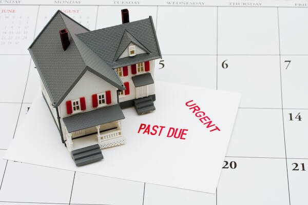 model house on top of calendar with past due mortgage statement underneath