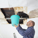 Man Collecting Water In Bucket From a water damaged Ceiling