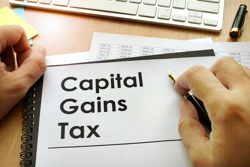 Hands holding documents with title capital gains tax text